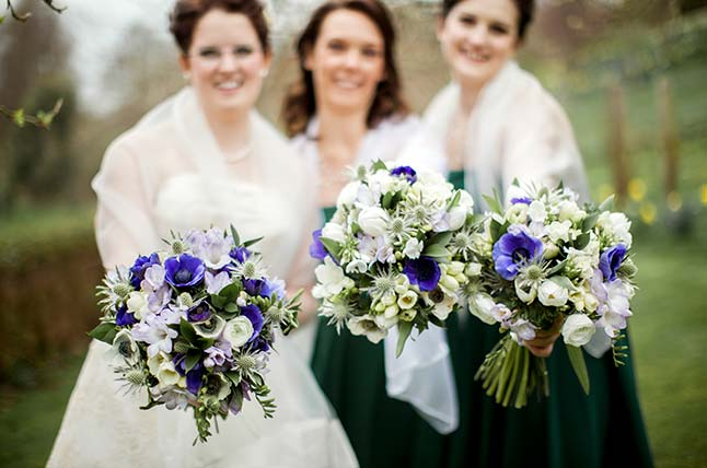 Bridesmaids holding fresh bespoke wedding bouquets, flowers pointing towards the camera
