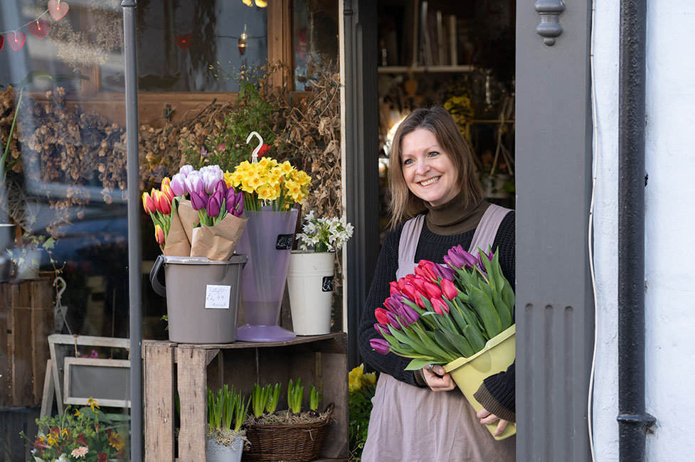 Jo from The Flower Shop Bruton smiling with fresh cut flowers