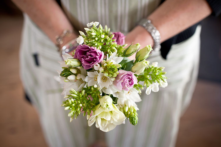 Girl holding a bespoke wedding bouquet - close up of fresh flowers and hands